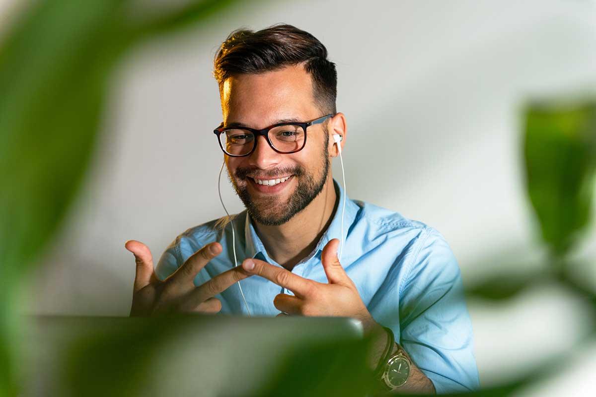 Mann macht am Laptop den kostenlosen NELA Online Audio Sprachtest