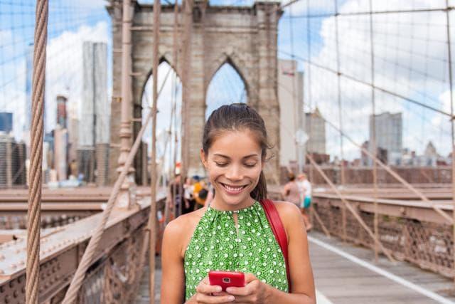 Englisch Sprachkurs Schülerin chattet mit dem Smartphone auf Englisch auf der Brooklyn Bridge